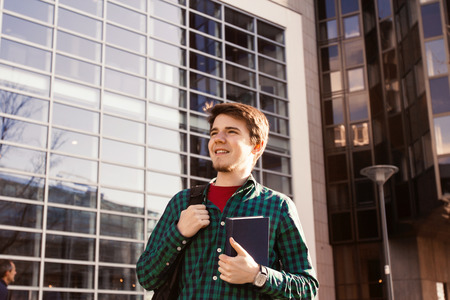 Smiling young student man holding a book and a bag on a university background .Young smiling student  outdoors Life style.City.Student. Stock Photo
