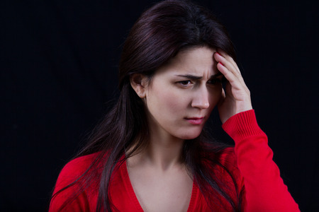 bothered: Stressed young women,student portrait, sad, bothered, holding hand on her head isolated on black background. Stock Photo