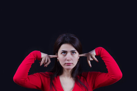 frustrated,bored young woman holding her ears, closing ears isolated on black background.