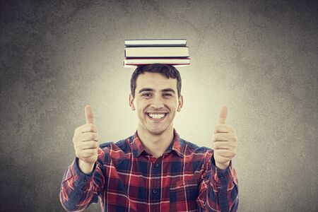 looking: Smiling excited young man with thumb up holding a stack of books on his head isolated on white background.Close-up shot of Happy smiling student with thumb up in shirt over white background.