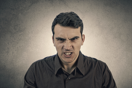 face to face: Stressed, aggressive, frustrated portrait of a young student, man isolated on grey background.Facial expression