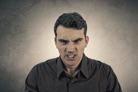 personas enojadas: Tensionado, agresivo, retrato frustrado de una joven estudiante, hombre aislado en la expresi�n background.Facial gris Foto de archivo
