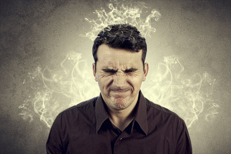 unhappy man: Portrait of Young man thinking too hard .Angry,Stressed man with waving smoke from head. Stock Photo