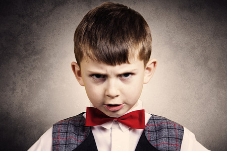 defiance: Stubborn, sad, upset little boy, child isolated over grey background.Facial expression