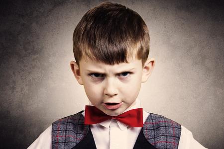 Terca, triste, molesto niño pequeño, niño aislado más de expresión background.Facial gris