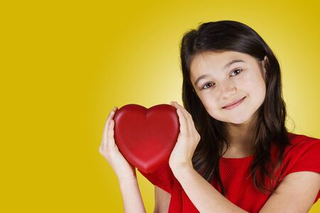 Happy, smiling little girl holding Red heart isolated on yellow background.Concept Love, Care, Health.Facial expression. Stock Photo