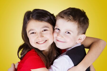 sister: Happy brother and sister hugging over yellow background.Love, Family, Friendship