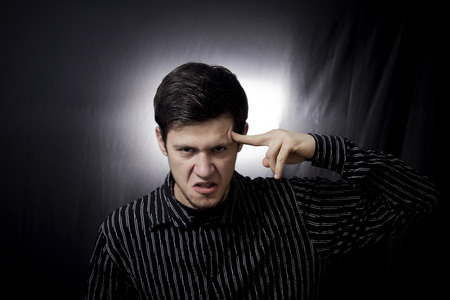 Stressed, aggressive portrait of a young student, man, pointing with finger to his had with harmful, mad look trying to remember something.Facial expression.Remember, memorizing.