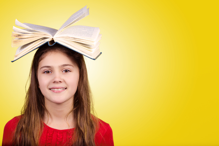 colegiala: Smiling Portrait of a cute little schoolgirl loving to learn with a open book on her head, isolated over yellow background.