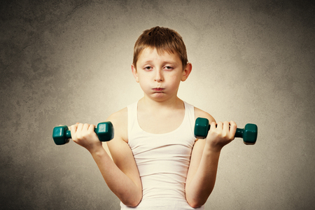 tired person: Tired, Bored, upset little boy with dumbbell.Facial expression, Sport.