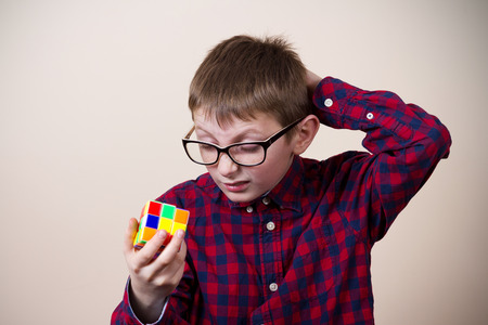 puzzling: Confused little boy nerd, holding a puzzle cube and a hand on his head.Concept, perplexed. Stock Photo