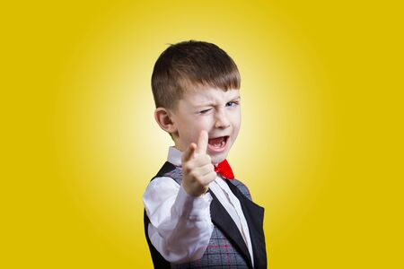 eye closed: Pointing to camera funny little boy with one eye closed isolated over yellow background. Stock Photo