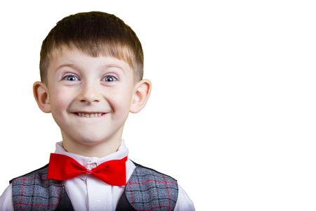 Smiling, Happy, Joyful beautiful little boy, looking at camera.Close-up Studio Portrait isolated on yellow background. Stock Photo