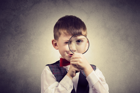 Curious Exploring little boy with magnifying glass, on yellow background. Stock Photo