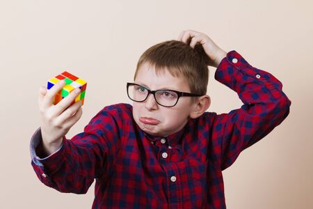 perplexed: Confused little boy nerd, holding a puzzle cube and a hand on his head.Concept, perplexed. Stock Photo