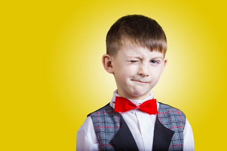 eye closed: Funny little boy with one eye closed isolated over yellow background.