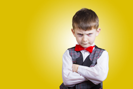 defiance: Stubborn, sad, upset little boy, child isolated over yellow background.Facial expression Stock Photo