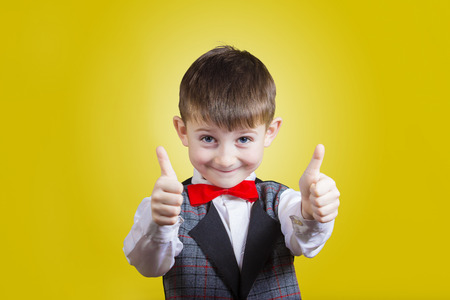 Excited Surprised  little boy with thumb up gesture isolated over yellow background.