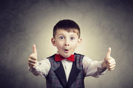 Opgewonden Verrast kleine jongen met duim omhoog gebaar geïsoleerd over grijze achtergrond.