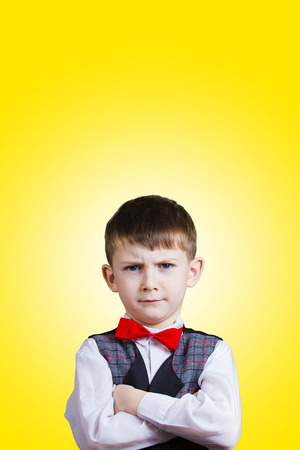 defiance: SeriousStubbornsadupset  little boychild  isolated over grey background.Facial expression