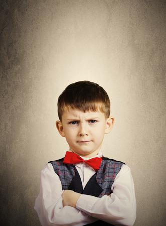 SeriousStubbornsadupset  little boychild  isolated over grey background.Facial expression
