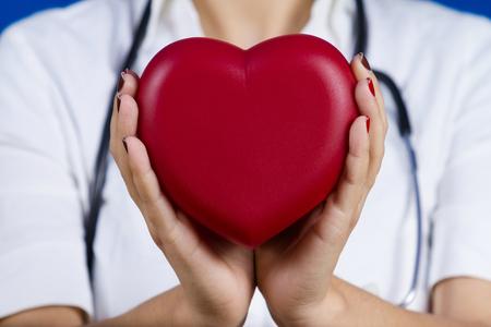 io: Female doctor holding red heart .Medicine, Health Care, Hospital.