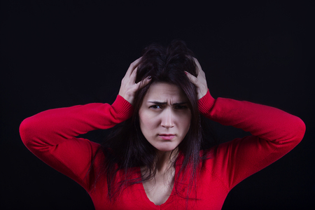 bothered: Stressed young women, student portrait, sad, bothered, holding hand on her head isolated on black background. Stock Photo