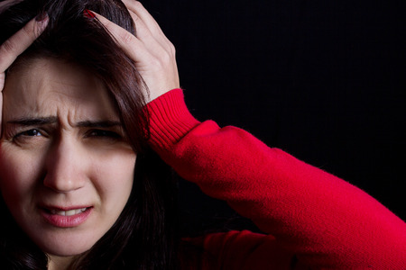 bothered: Stressed young womenstudent portrait sad bothered holding hand on her head isolated on black background. Stock Photo