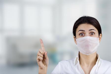 Female doctor with protective mask pointing up.HospitalPreventionStopMedicalHospitalDanger.