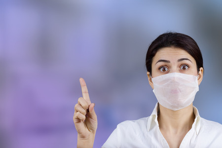 Female doctor with protective mask pointing up.HospitalPreventionStopMedicalHospitalDanger.