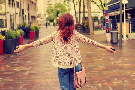 mujer de la libertad joven con las manos levantadas en una mujer city.Young caminando con las manos levantadas estilo free.Life sensación