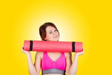 Sporty fit healthy smiling beautiful woman red head girl holding  an yoga mat.Exercise fitness.Woman standing holding yoga mat isolated on yellow background. photo
