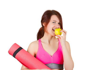 Sporty fit healthy smiling beautiful woman red head girl holds an apple and yoga mat.Exercise fitness.Woman standing holding yoga mat isolated on white background. photo