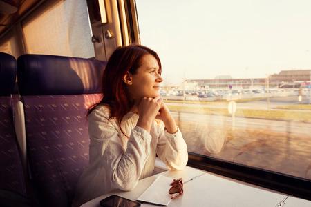 기차에 앉아있는 동안 젊은 여자 창 밖을보고 여행입니다. 스톡 콘텐츠