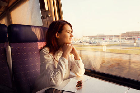tren: Mujer joven que viaja mirando por la ventana mientras se est� sentado en el tren. Foto de archivo