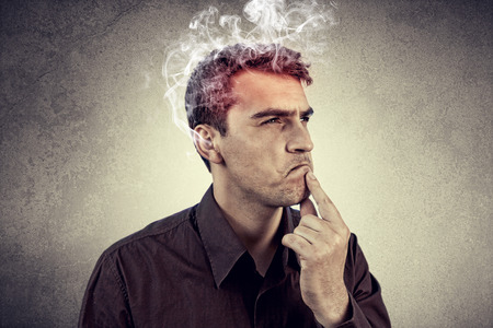 Portrait of Young man intensively thinking too hard with waving smoke from head.