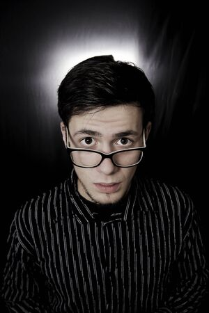 eyes wide: Portrait of a young studentman with eyes wide opened wearing black glasses with amazed facial expression isolated black background. Stock Photo