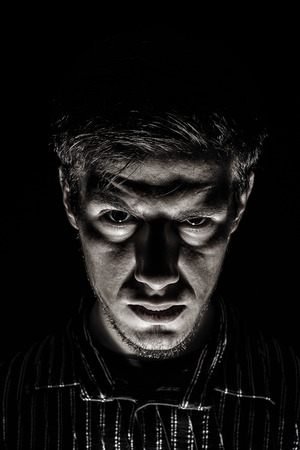 psychotic: Man portrait with evil look isolated on black background.Face expression