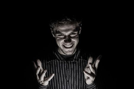 Man portrait with evil look isolated on black background.Face expression