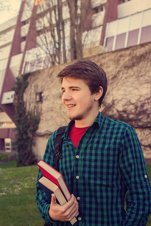university life: University.Smiling young student man holding a book and a bag on a university background .Young smiling student  outdoors Life style.City.Student. Stock Photo