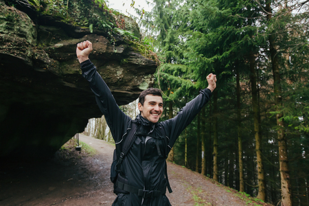 Young Man,Student with raised hands hiking in forest.Man hiker smiling happy portrait holding hands up enjoying nature on foggy day during a trekking trip. Back of a young man outdoors in nature on a hiker path in forest.