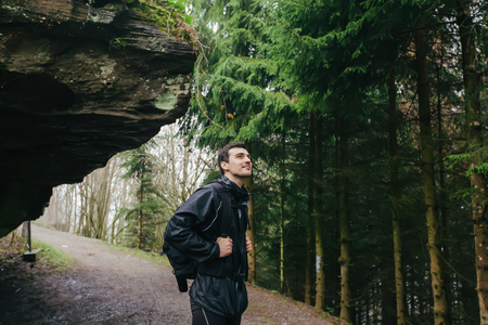 Young Man,Student hiking in forest.Man hiker smiling happy portrait looking up enjoying nature on foggy day during a trekking trip. Back of a young man outdoors in nature on a hiker path in forest.