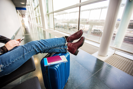 Passenger traveler woman using tablet smart phone in airport waiting for air travel .Young woman sitting with travel suitcase trolley, in waiting hall of departure lounge in airport Stock Photo