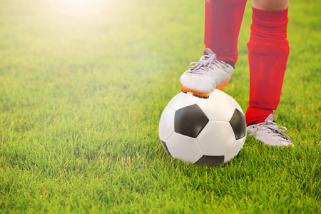 Close-up of little boy leg playing football on football pitch.Soccer,football Training on a football field. Stock Photo