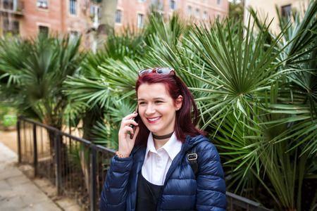 Happy smiling tourist woman talking on the phone outdoor in Barcelona.Traveling young woman talking on the phone.Technology