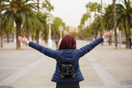 Freedom-Young woman with raised hands in a city.Young tourist woman walking with raised hands feeling free in Barcelona.Life style