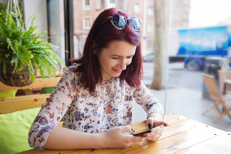 Young tourist woman using smartphone in restaurant waiting for her morning coffe.Tourist Girl texting on the smart phone in a restaurant.