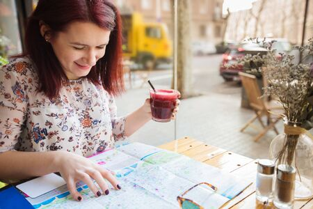 Young tourist girl drinking morning smoothie in a restaurant and planing her trip with a tourist map.Travel.Tourist map guide