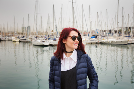 Young pretty tourist woman walking on wooden pier near sea and looking at the city. Attractive hipster girl enjoying her holidays in Spain Barcelona. Stock Photo