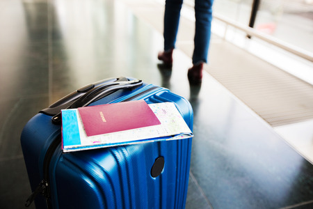 Traveling luggage in airport terminal with passport and a tourist map.